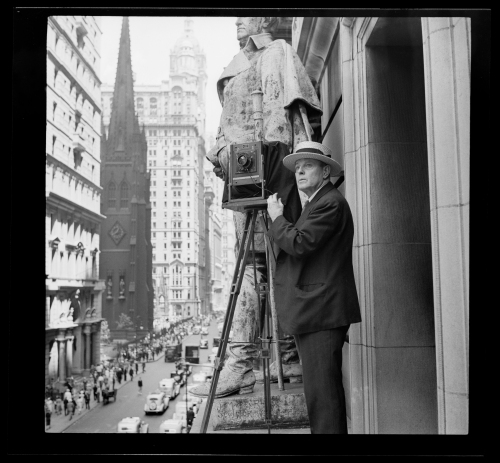 Wurts Bros. Broadway and Exchange Place. Norman Wurts making photos from 4th-story ledge on Exchange Court Building, 1937. Museum of the City of New York. X2010.7.1.8427
