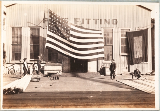 Morse Dry Dock and Repair Company. Employees Association of Morse Dry Dock and Repair Co. [Flag being raised at the Pipe Fitting Shop.]. 1919. Museum of the City of New York. F2013.131.31.