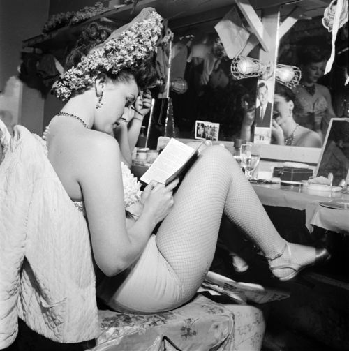 James Godbold for LOOK Magazine. Night Clubs- Copa Showgirls [Showgirl reading backstage.] 1950. Museum of the City of New York. X2011.4.12052.14.