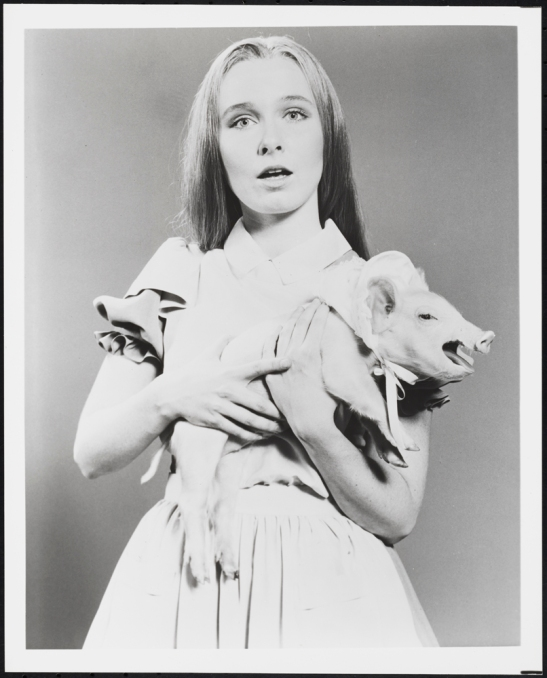 "[Kate Burton as Alice with the pig in ""Alice in Wonderland"".]"