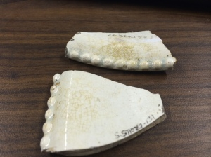 Because of the curve of these rim fragments, archaeologists are able to identify them as part of a 19th century baker. Image courtesy of the author.
