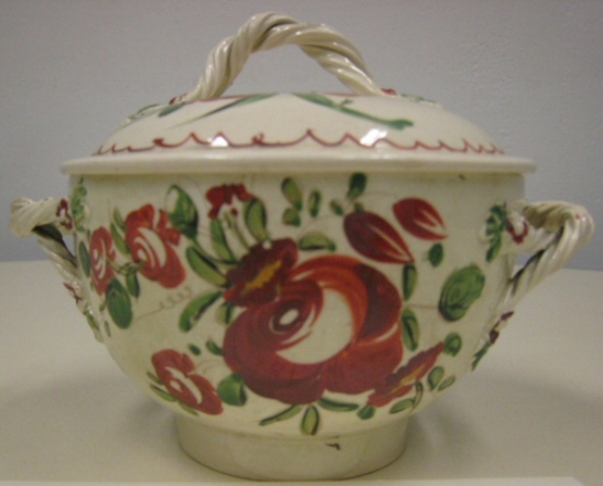 Cream-colored earthenware sugar bowl from tea service with enamel decoration of large red roses and polychrome leaves and flowers, twisted handle on each side and circular cover with same twisted handle at the top center.