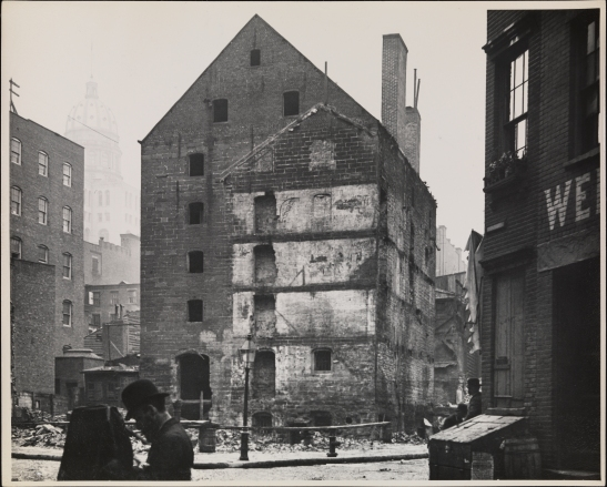 View of the Rhinelander Sugar House at the corner of Rose Street and Duane Street after a fire  Another photographer is visible in the foreground.