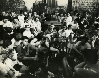 """View of young people gathered around three people playing guitar at Washington Square Park. """"4-22-62 / Musicians in Washington Square / Plus-x: 1/200 sec. f8 / IIIf / 21mm f4 Super Angulon"""" in pencil upper left, verso"""