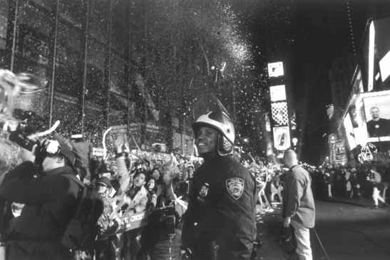 A smiling police officer is watching the screaming crowd celebrating New Year's Eve 1997 behind police lines on Times Square.