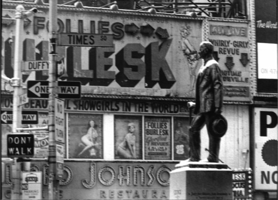 "View of Times Square at Broadway and W. 46th Street and of the Father Duffy Statue in front of Howard Johnson's Restaurant in 1967.  Signs above the Howard Johnson's say ""[M]os[t] Beau[tifu]l Showgirls in the World"", and ""All Live Whirly=Girly Revue plus BigTime VaudeVille."""