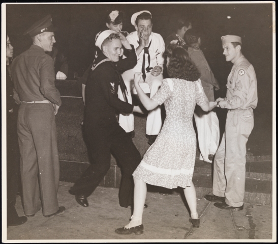 Mary Gets Going. [Soldiers and girl dancing in Times Square.]