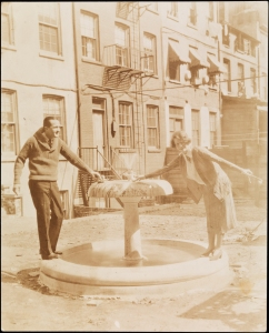Unidentified man and Jessie Tarbox Beals. Edna St. Vincent Millay standing near fountain in Greenwich Village, ca. 1922. Museum of the City of New York, 94.104.862.