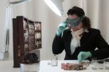 Conservator Linda Niewenhuizen at work on the King family medicine dispensary.